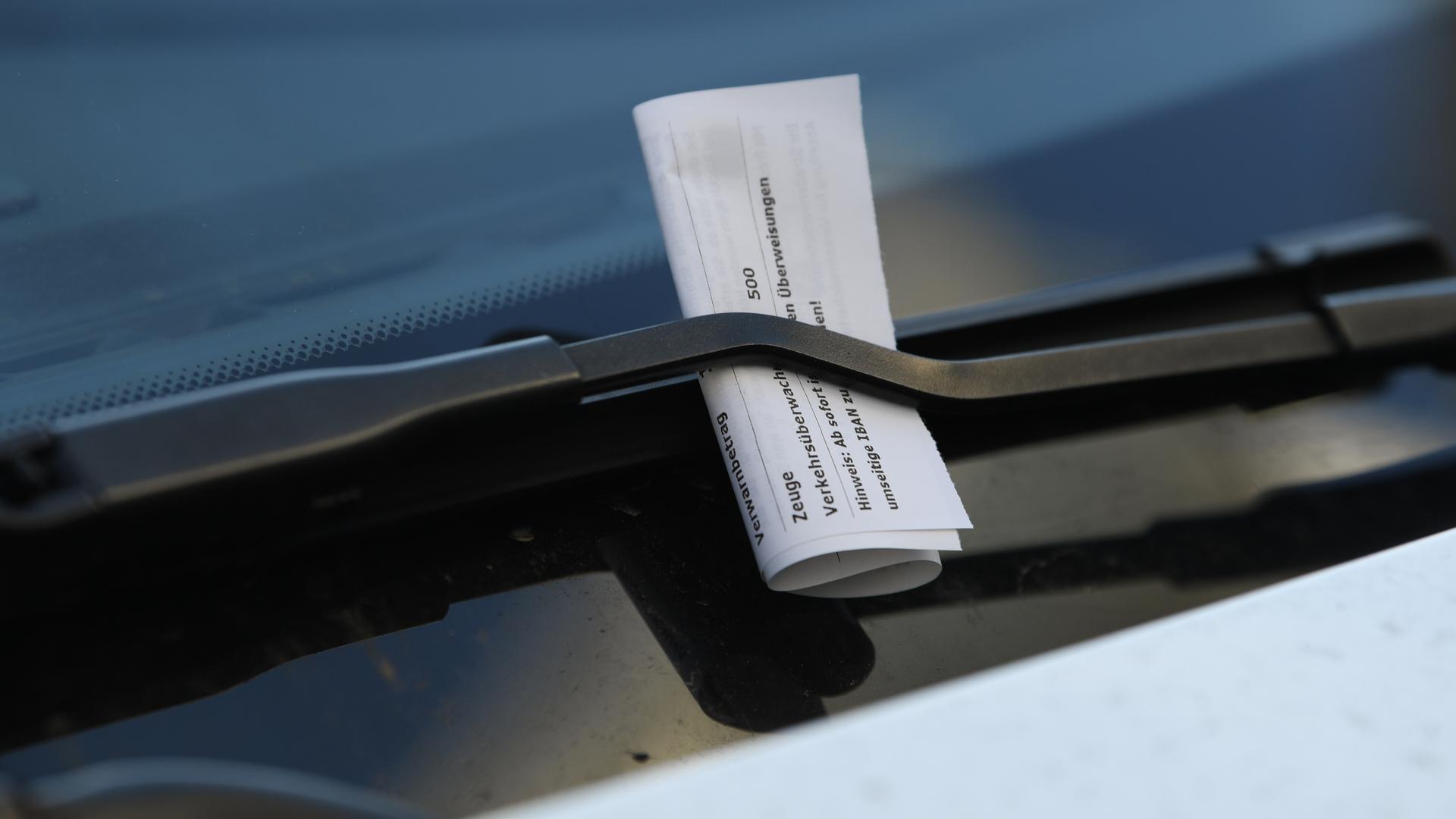 Ein Strafzettel klemmt an einem Auto in der Frankfurter Innenstadt an einem Scheibenwischer. (zu dpa «Klingelnde Kassen: Verkehrssünder sorgen für mehr Knöllchen-Einnahmen») +++ dpa-Bildfunk +++