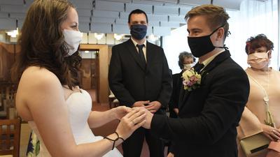 Eine Braut und ihr Bräutigam mit Mundschutz tauschen bei ihrer Trauung auf dem Standesamt die Ringe.