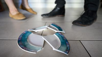 ILLUSTRATION - Ein Mann und eine Frau stehen hinter einem zerbrochenen Teller in einer Küche. (zu dpa «FDP rügt Mangel an Schutz für Opfer häuslicher Gewalt») +++ dpa-Bildfunk +++