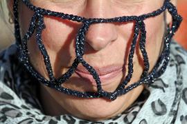 """Eine Teilnehmerin einer """"Querdenken""""-Demonstration gegen die Anti-Corona-Maßnahmen trägt ein Netzgeflecht vor Mund und Nase. Die Kundgebung der Initiative """"Querdenken 721"""" auf dem Karlsruher Messplatz stand unter dem Motto """"Freiheit, Frieden, Gerechtigkeit und Liebe""""."""
