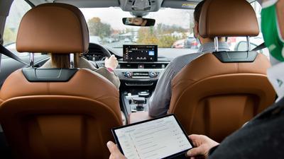 Ein Fahrprüfer hält ein Tablet mit einem elektronischen Prüfprotokoll in der Hand (gestellte Szene).