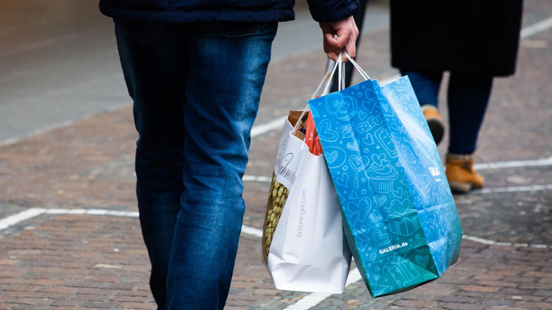 """Ein Mann trägt Einkaufstüten durch die Innenstadt. Viele Menschen nutzten den zweiten Adventssamstag für Weihnachtseinkäufe. (Zu dpa """"Credit Suisse: Geschäft mit Schweizer Einkaufstouristen eingebrochen"""") +++ dpa-Bildfunk +++"""