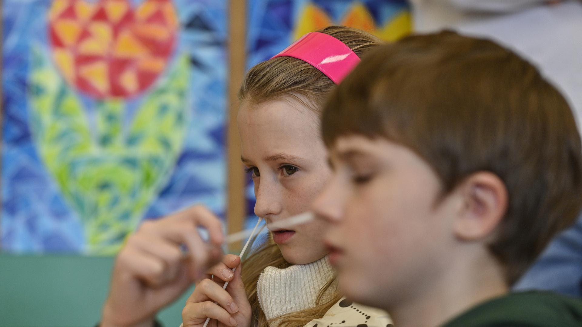 Zwei Schulkind führen in einem Klassenraum einen Corona-Schnelltest bei sich durch. Im Zusammenhang mit einem Projekt, haben die Kinder sich selbst in den Klassenzimmern in Prag mit einem Coronaschnelltest auf eine Coronainfektion getestet. +++ dpa-Bildfunk +++