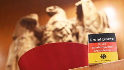 ILLUSTRATION - Vor dem Bundesadler im Sitzungssaal des Bundesverfassungsgericht steht eine Miniaturausgabe des Grundgesetz für die Bundesrepublik Deutschland sowie ein Barett eines Bundesverfassungsrichters. Im September 2021 feiert das Bundesverfassungsgericht seinen 70. Geburtstag. +++ dpa-Bildfunk +++