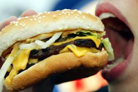 """ARCHIV - Eine junge Frau isst am 23.01.2003 in Düsseldorf einen Hamburger. Das höchste Gremium der Weltgesundheitsorganisation (WHO) berät bis zum 24. Mai unter anderem über Maßnahmen gegen die Ausbreitung nicht übertragbarer Krankheiten wie Diabetes, Krebs, Herzleiden oder Fettsucht. Viele solcher Krankheiten werden durch ungesunde Ernährung begünstigt oder hervorgerufen. Foto: Gero Breloer/dpa (zu dpa """"UN-Beauftragter regt Konvention gegen ungesunde Ernährung an"""" vom 19.05.2014) +++ dpa-Bildfunk +++"""