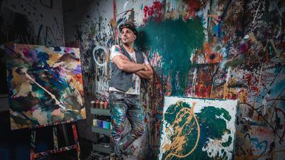 Mann steht neben Kunstwerken
