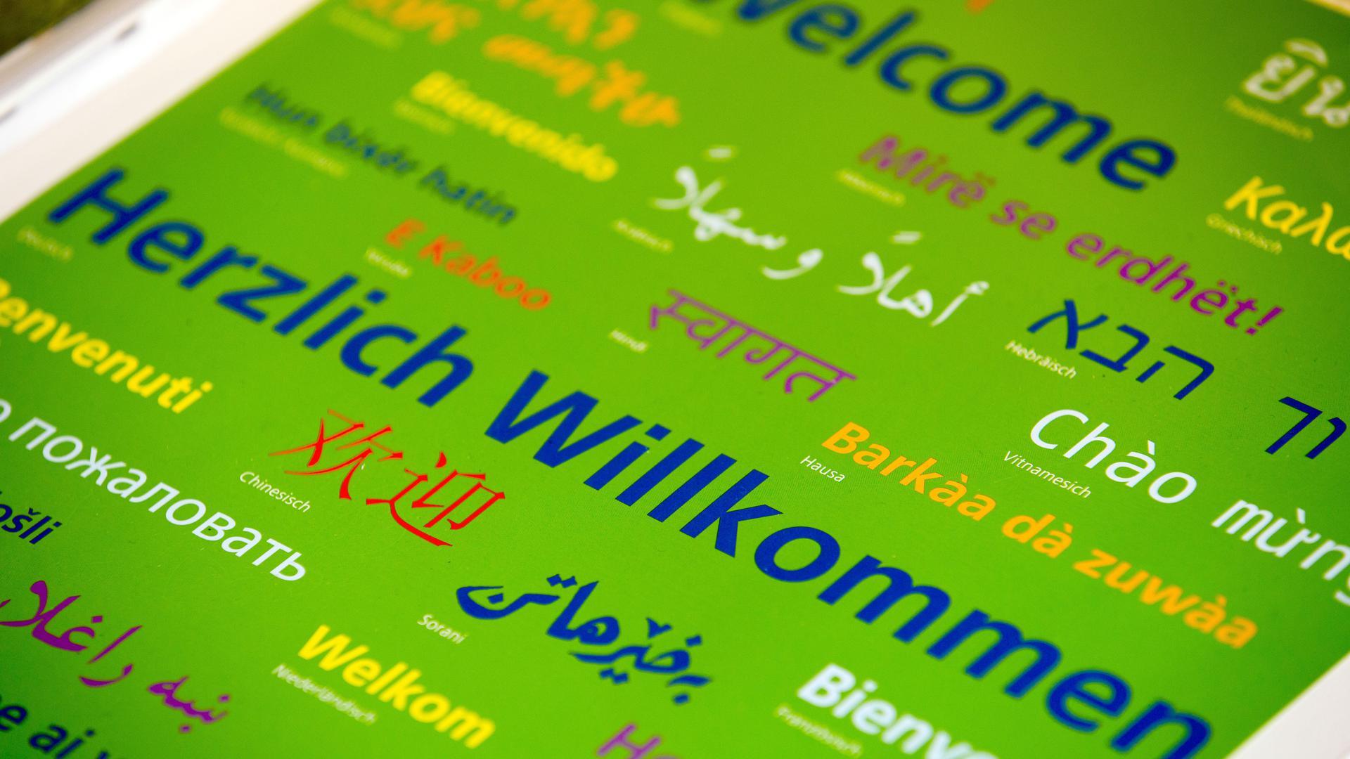 """ARCHIV- """"Herzlich Willkommen"""" ist am 18.03.2015 in verschiedenen Sprachen auf einem Deckblatt von Arbeitsmaterialien für den Deutschunterricht für Flüchtlingskinder zu lesen. Foto: Jens Büttner/dpa (zu lrs """"Willkommenskultur als Wettbewerbsvorteil"""" vom 13.04.2015) +++ dpa-Bildfunk +++"""