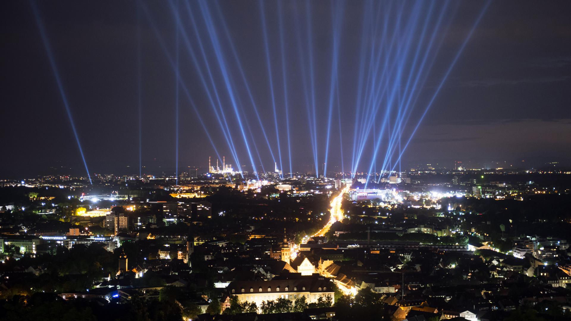 Bei einem Probelauf strahlen 32 Lichtsäulen am 16.06.2015 über Karlsruhe (Baden-Württemberg) in den Nachthimmel. Die Lichtinstallation ist Teil des viertägigen Eröffnungsfestival zum 300. Stadtgeburtstag, das am 17.06.2015 beginnt. Jede Lichtsäule steht für eine historische Persönlichkeit, die in Karlsruhe gewirkt hat oder in der Stadt geboren ist. Die Lichtsäulen sind auch in den beiden folgenden Nächten, am 18. und 19. Juni 2015, zu sehen. Foto: Uli Deck/dpa ++ +++ dpa-Bildfunk +++
