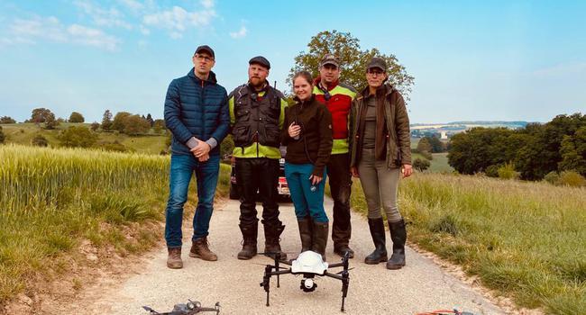 Fünf Menschen stehen auf einem Feld
