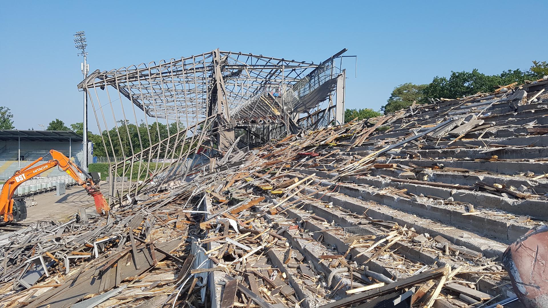 Die Osttribüne im KSC-Stadion in Karlsruhe ist zum Teil abgerissen, ein Bagger steht davor.