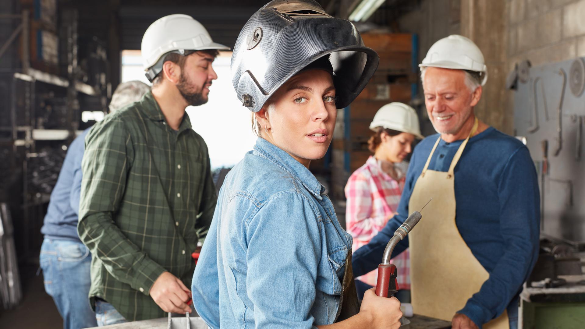 Junge Frau mit Schutzhelm macht eine Lehre als Schweißer in einem Industriebetrieb.