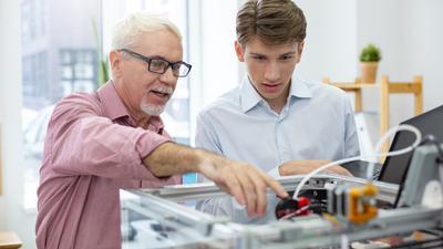 Älterer Mitarbeiter erklärt jungem Praktikanten die Arbeit.