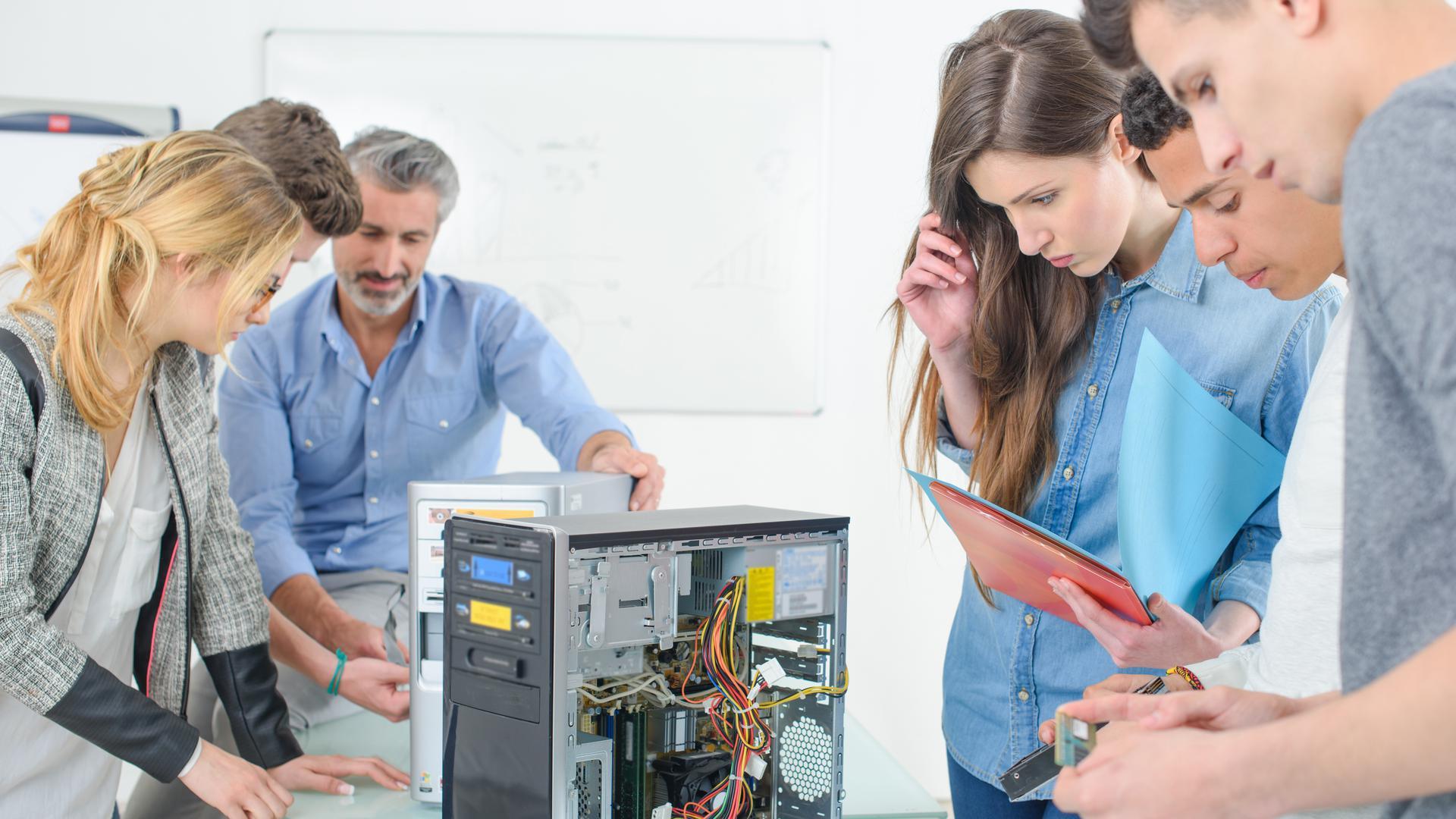 Tutor and Studenten reparieren einen Computer.