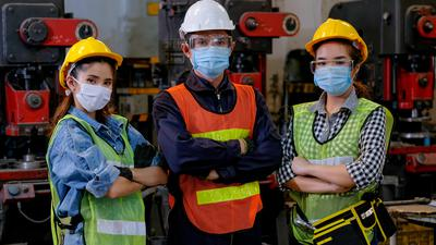 Gruppe von Handwerkern mit Mundschutz.