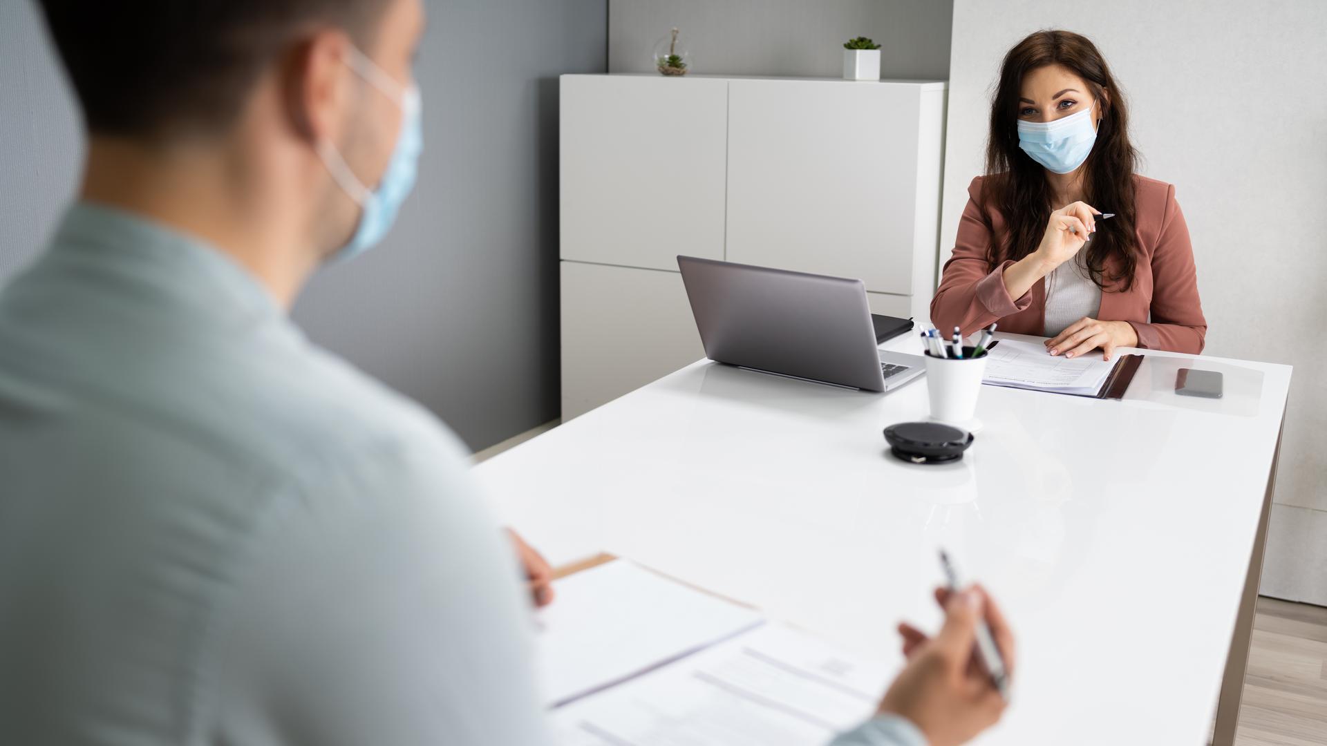 Bewerbungsgespräch mit Abstand und Mundschutz.