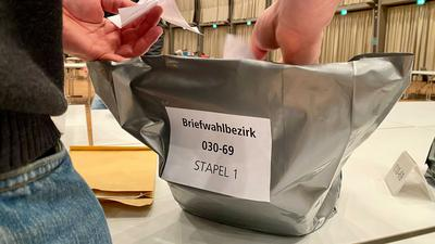 Ein Wahlhelfer versiegelt Stimmzettel der Briefwahl bei der OB-Wahl in Karlsruhe.