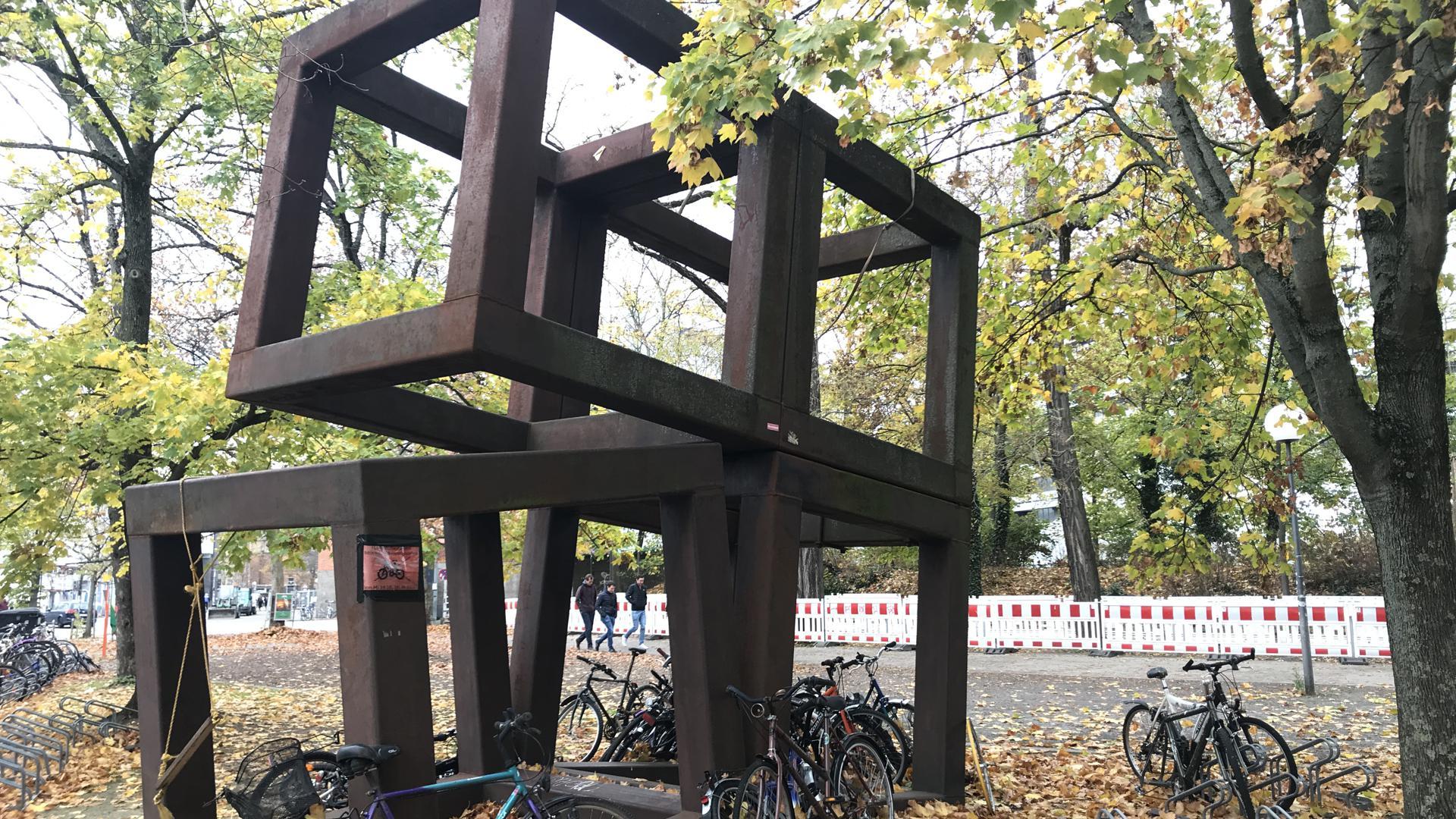 """Minimalistische Gitterkomposition: Vor der KIT-Bibliothek steht die Stahlskulptur """"10/1972"""" von Alf Lechner – dass es sich hierbei um Kunst handelt, scheint so mancher Radfahrer, der seinen Drahtesel dort anlehnt, nicht zu bemerken."""