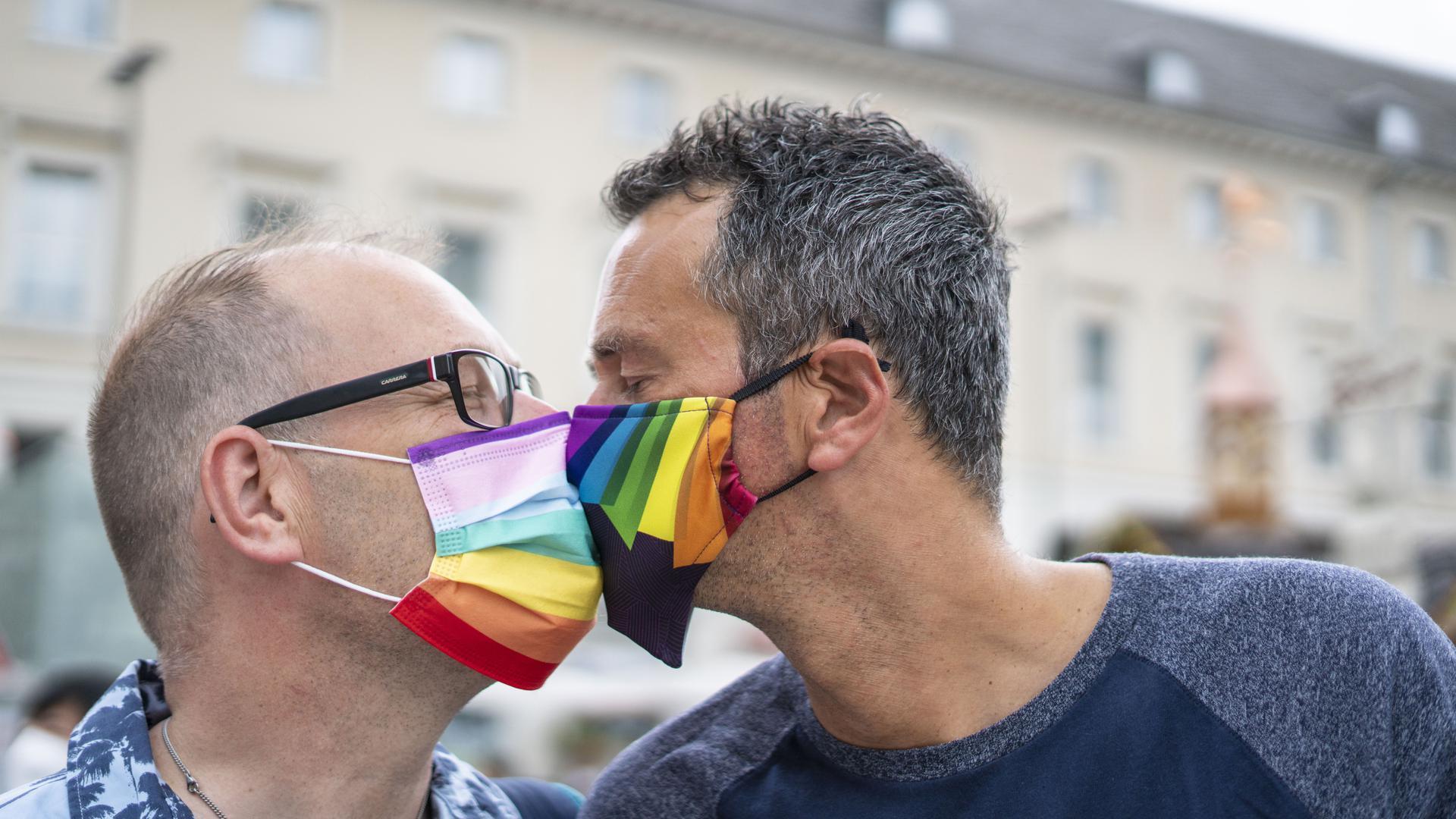 Zwei Männer mit Regenbogenmaske küssen sich.