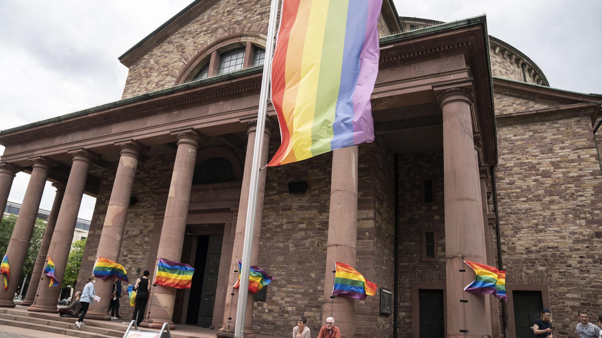 An der Karlsruher St.-Stephan-Kirche hängen Regenbogenflaggen.