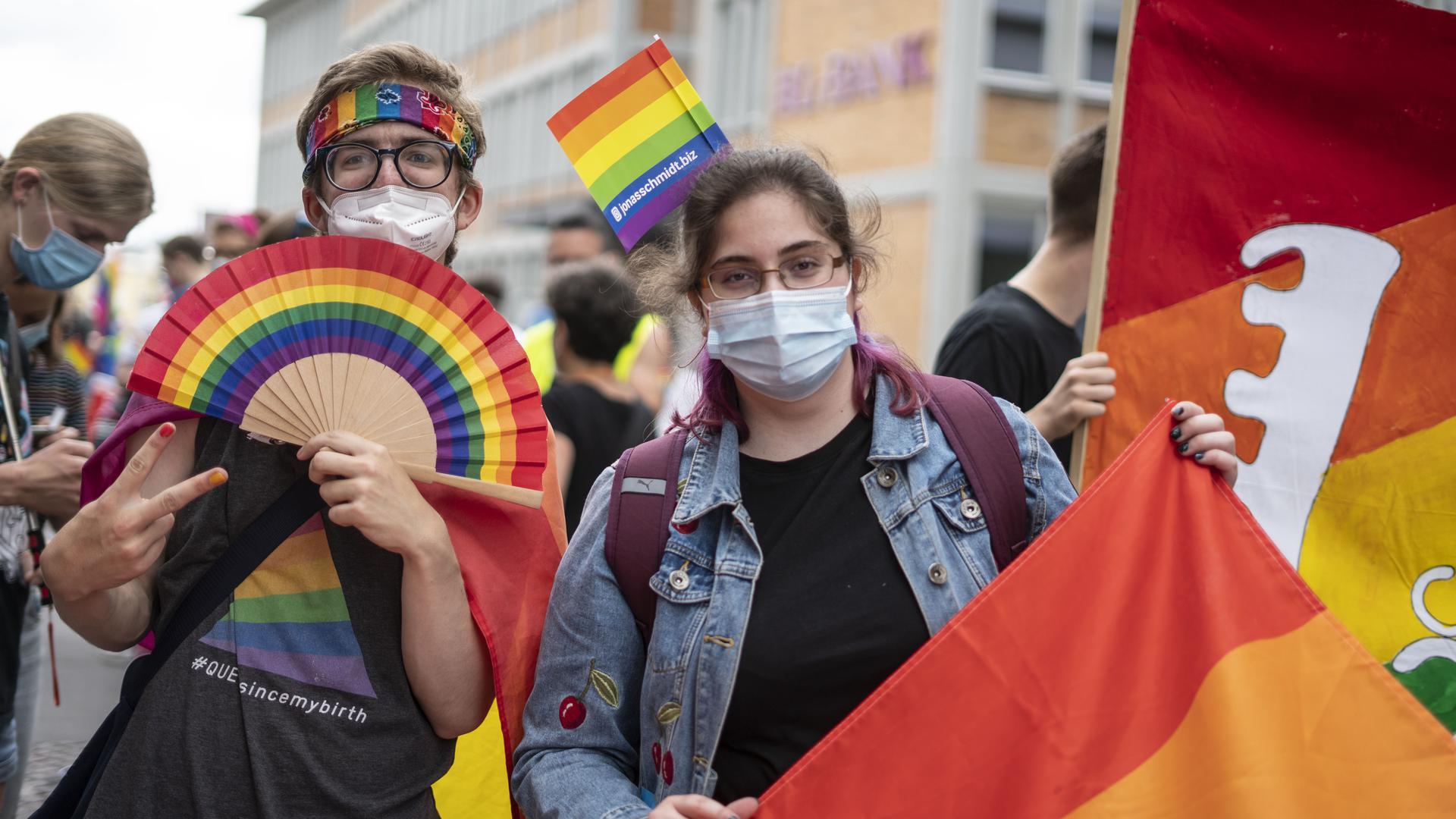 Zwei Menschen tragen regenbogenfarbene Kleidung