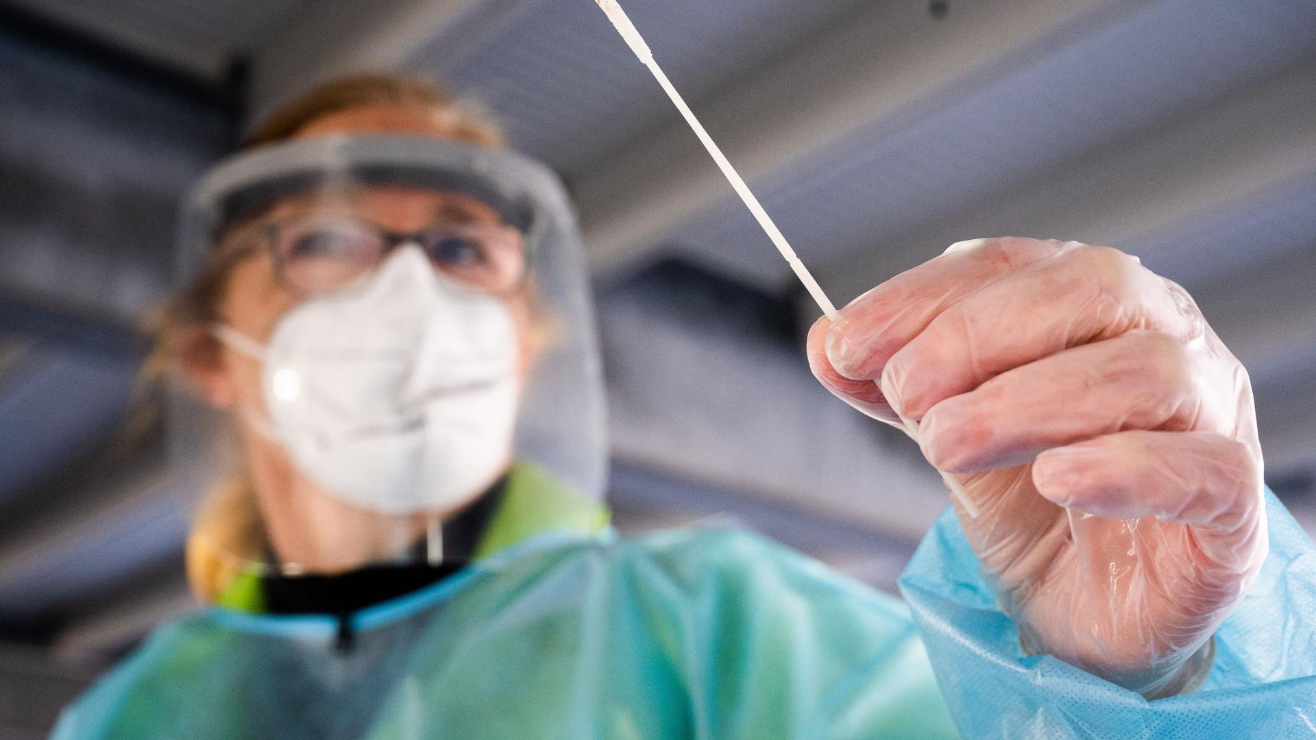 """Eine Helferin hält einen Teststab im """"Testzentrum am Zoo"""" bei einem Schnelltest auf das Coronavirus. Das Robert Koch-Institut (RKI) vermeldet weiterhin steigende Corona-Neuinfektionen in Deutschland. +++ dpa-Bildfunk +++"""