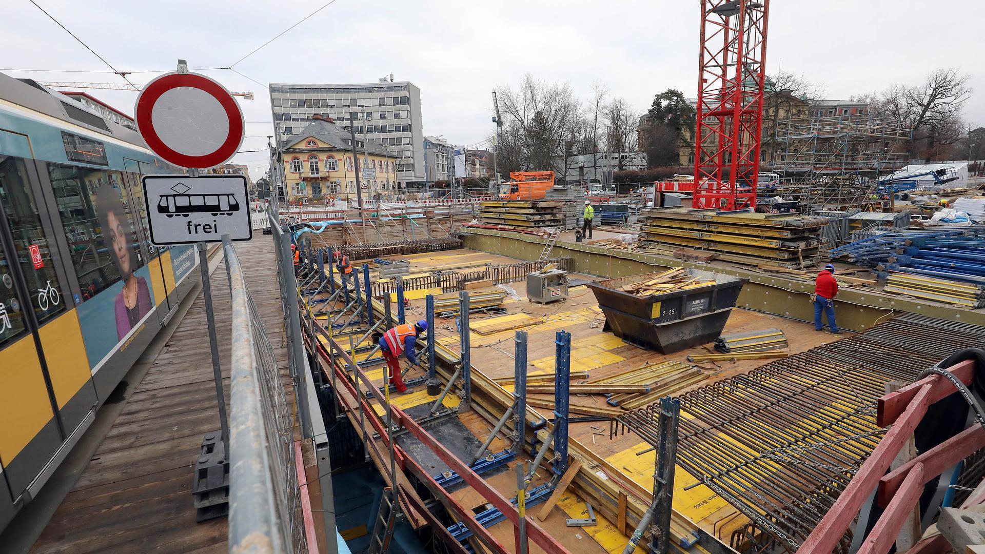 Über der Baugrube: Am Karlstor rollt die Straßenbahn über eine Behelfsbrücke, während die Arbeiter das Betonieren des letzten Stücks vom Tunneldeckel daneben vorbereiten.