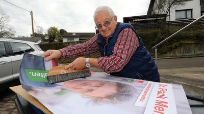 Franz Bitto klebt ein Wahlplakat des OB-Kandidaten Frank Mentrup auf.