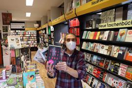 Belletristik und Satire: Christoph Schön steht vor den Regalen in der Buchhandlung Stephanus und hält seine drei Buchtipps für den Herbst 2020 in die Kamera.