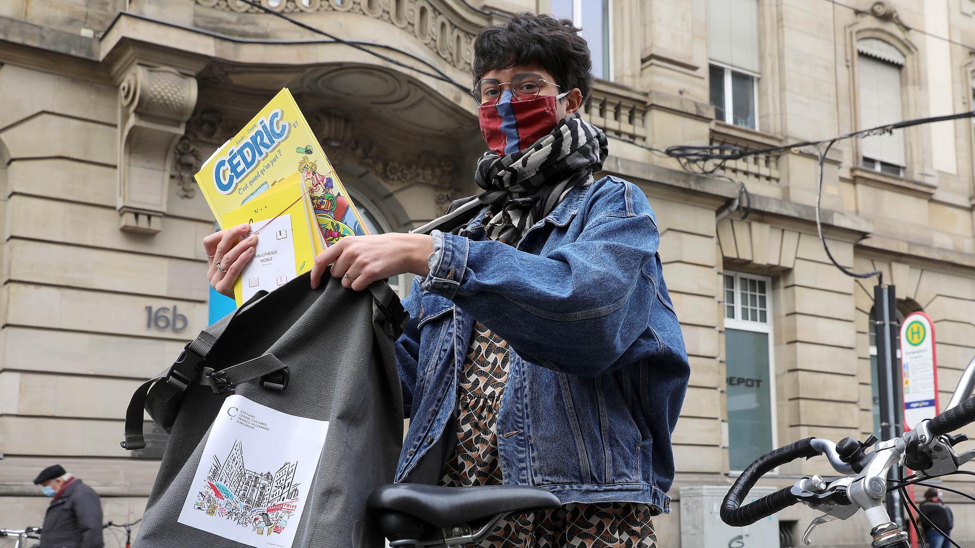 CCFA-Volontärin Cloé Miglioli packt eine Bestellung von Büchern aus der Mediathek in ihre Fahrradtasche.