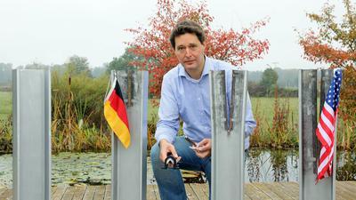 David Domjahn posiert hockend hinter einem seiner Kunstwerke, das aus vier unterschiedlich gespaltenen Stahlträgern besteht.