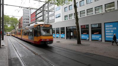 in der Kaiserstraße fährt eine Straßenbahn vor verhangene Ladenfenstern vorbei.