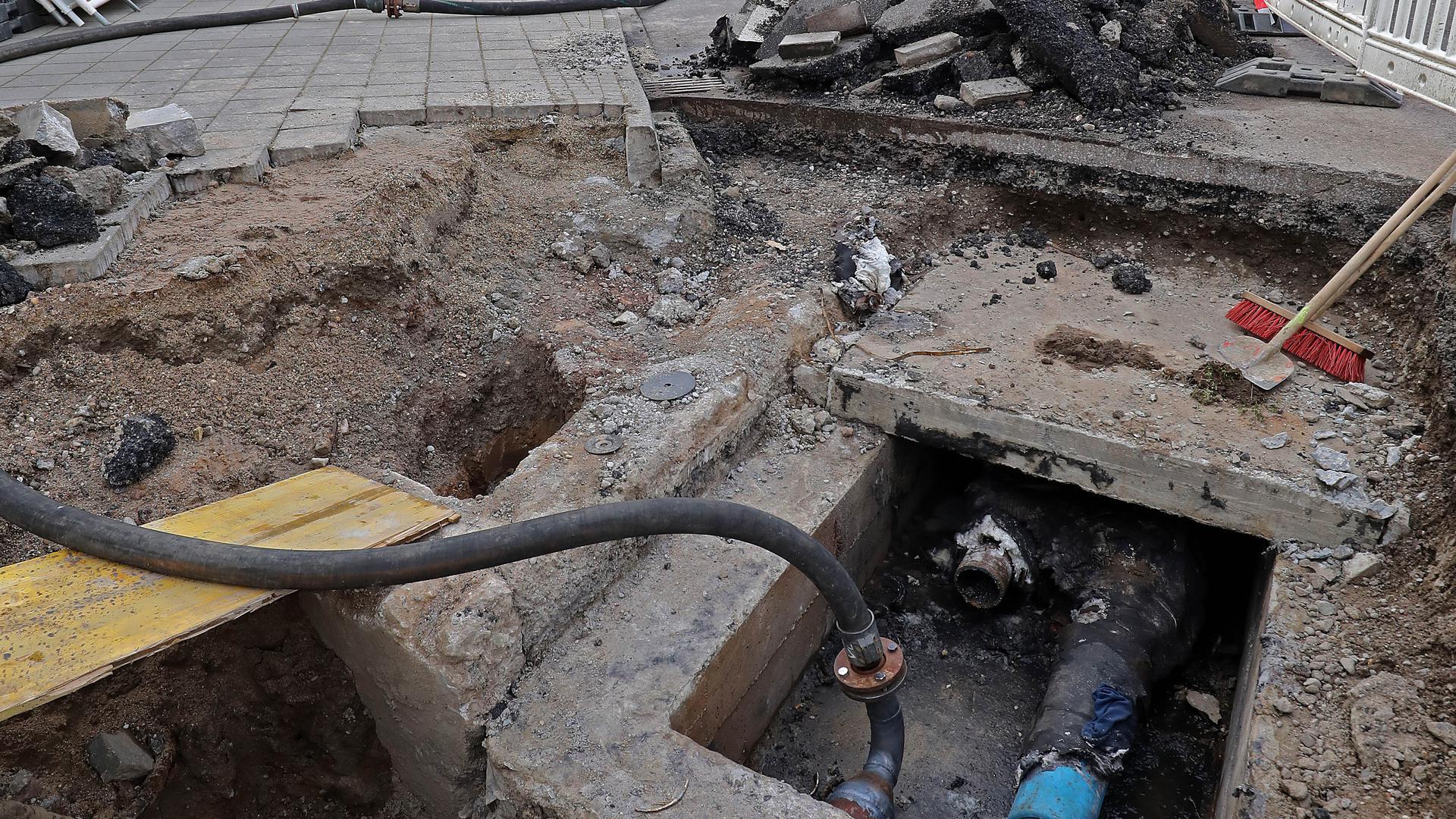 Ein Loch auf der Straße: Am Kreisel in der Karlsruher Sophienstraße ist in einer Grube die Stelle des Rohrbruchs freigelegt. Der Fernwärmeleitung wurde provisorisch mit einem Schlauch geflickt.