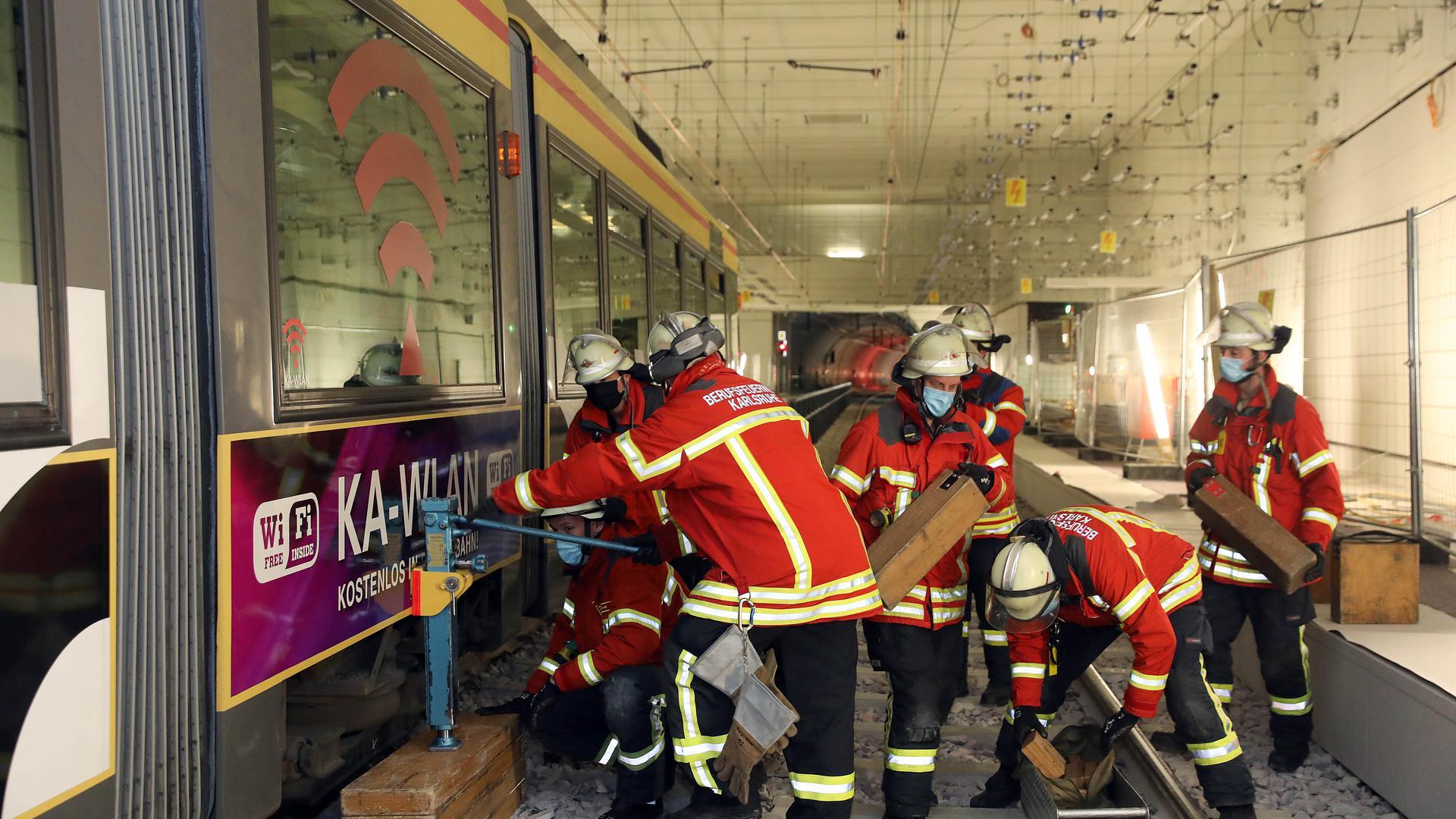 Im Tunneleinsatz: Die Feuerwehrleute befreien bei einer Übung in der U-Strab-Station Marktplatz eine Puppe, die unter dem Niederflurwagen eingeklemmt ist.