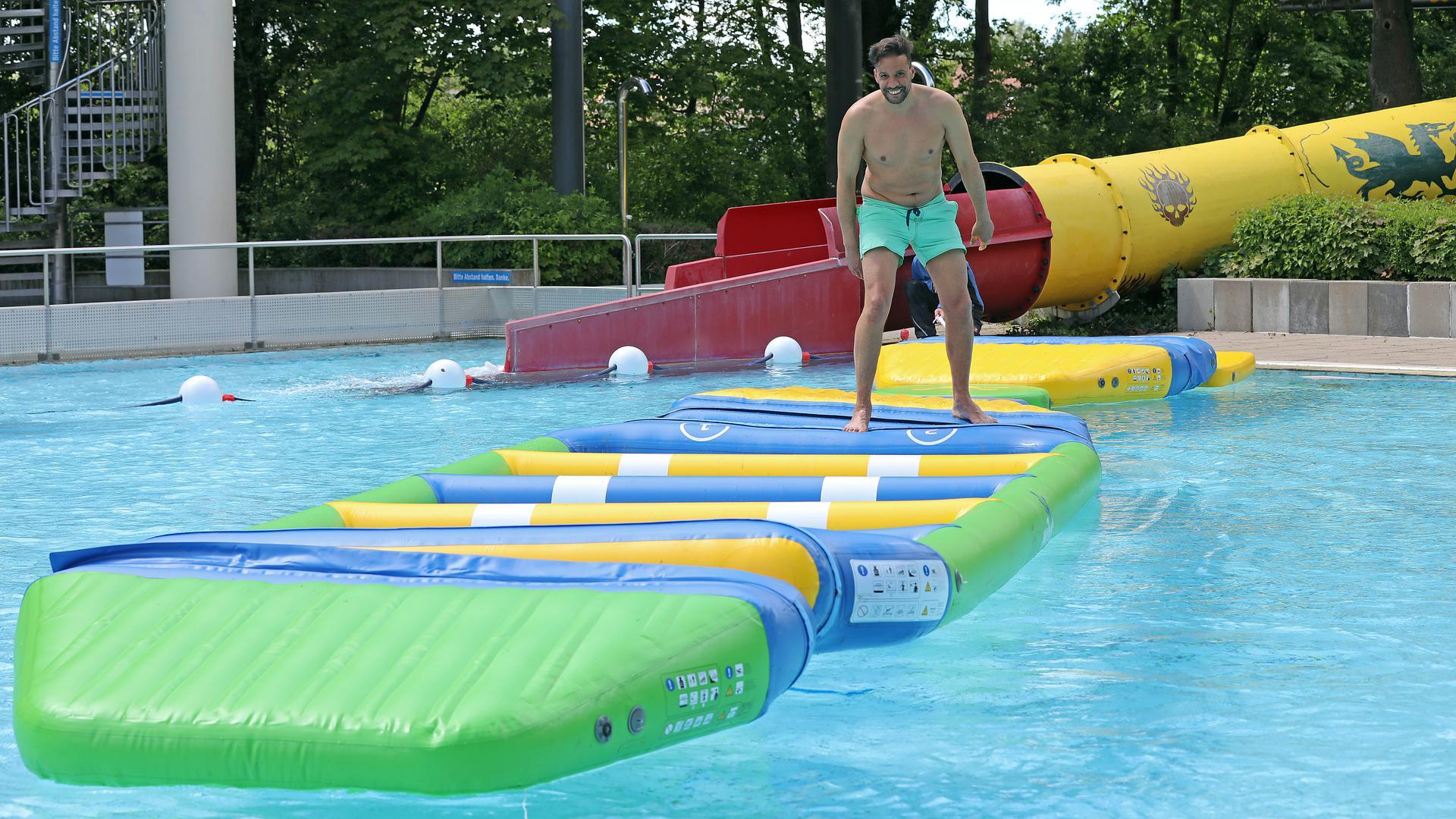 """Auf dem """"Aquatrack"""" können Besucher im Freibad Rüppurr über Wasser gehen. Dass das geht, zeigt probehalber Schwimm-Meister Amine Cherradi."""