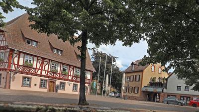 Am 10. August 2021  spiegelt sich das frisch restaurierte Rathaus in Grötzingen nur im Wasser des Brunnens auf dem Platz. Hochwassermarken verraten aber, wie verheerend früher Überflutungen durch die Pfinz waren.
