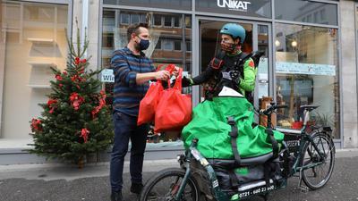 Übergabe vor dem Geschäft: Unikat-Inhaber Andreas Preißler händigt dem Radkurier Bestellungen aus. Die Lieferung ist für die Kunden im Stadtgebiet kostenfrei.
