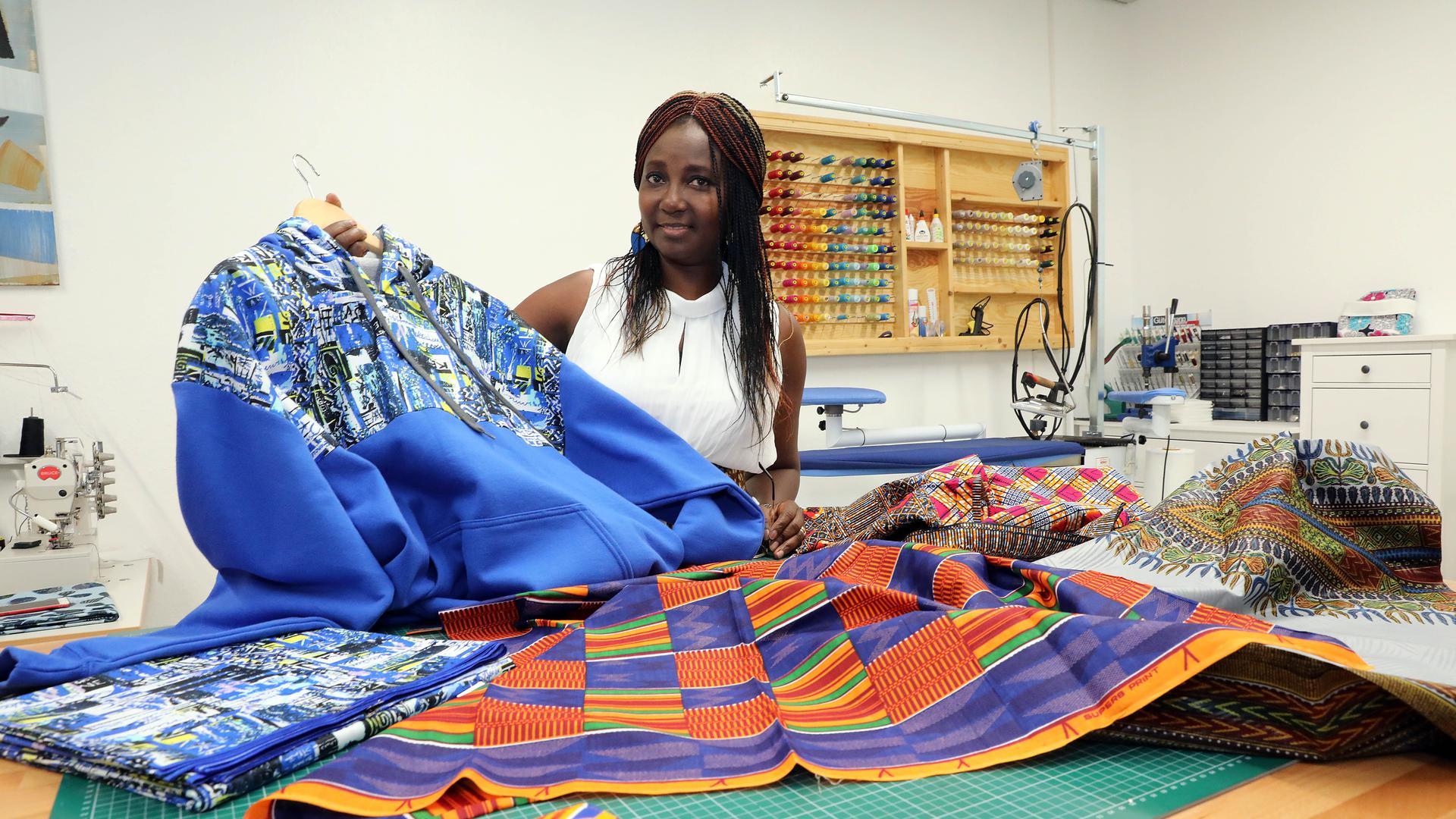 Pauline Nikolai steht hinter ihrem Arbeitstisch, auf dem verschiedene afrikanische Stoffe ausliegen.