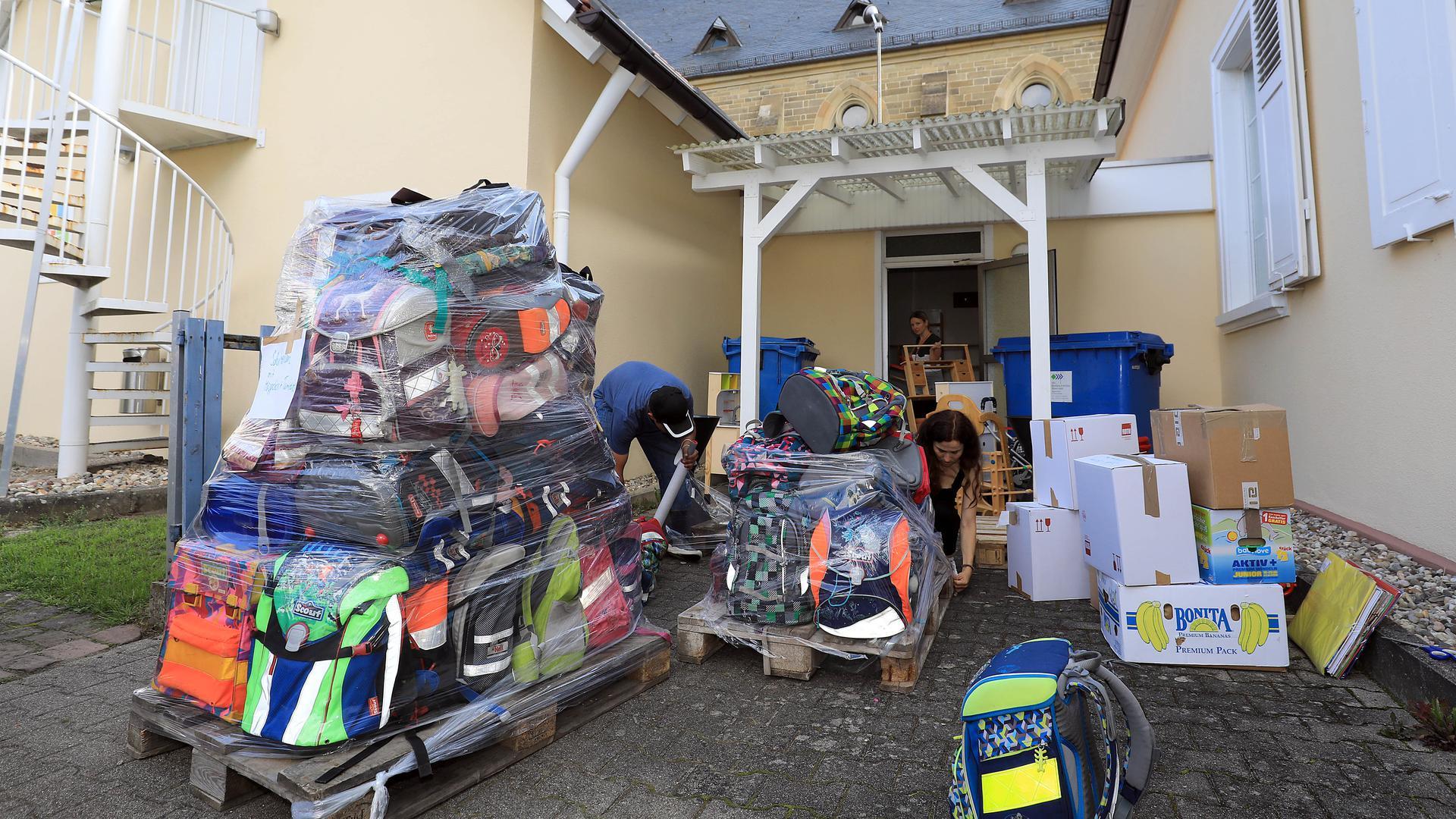 Gespendete Schulranzen stehen zusammengepackt zum Abtransport bereit