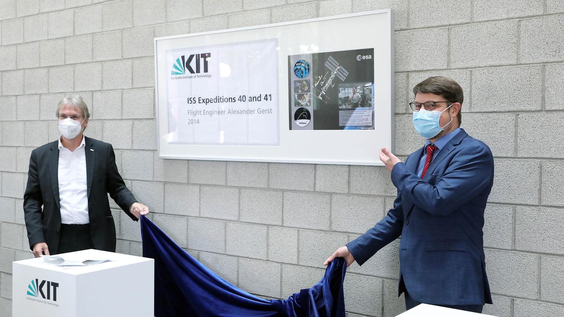 Die Fahne mit dem KIT-Logo hat den weltweit bekannten deutschen Astronauten Alexander Gerst 2014 bei seiner Reise ins All begleitet. Der Präsident des KIT Holger Hanselka und der Direktor der Bibliothek Arne Upmeier haben am Freitagmittag die Fahne beim Eingang der Bibliothek enthüllt.