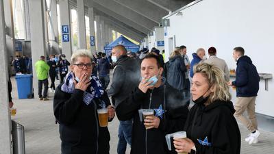 """Da auf den Tribünen Rauchverbot gilt, müssen auch diese drei Fans vom Fanclub """"Blauer Stern"""" ausweichen."""