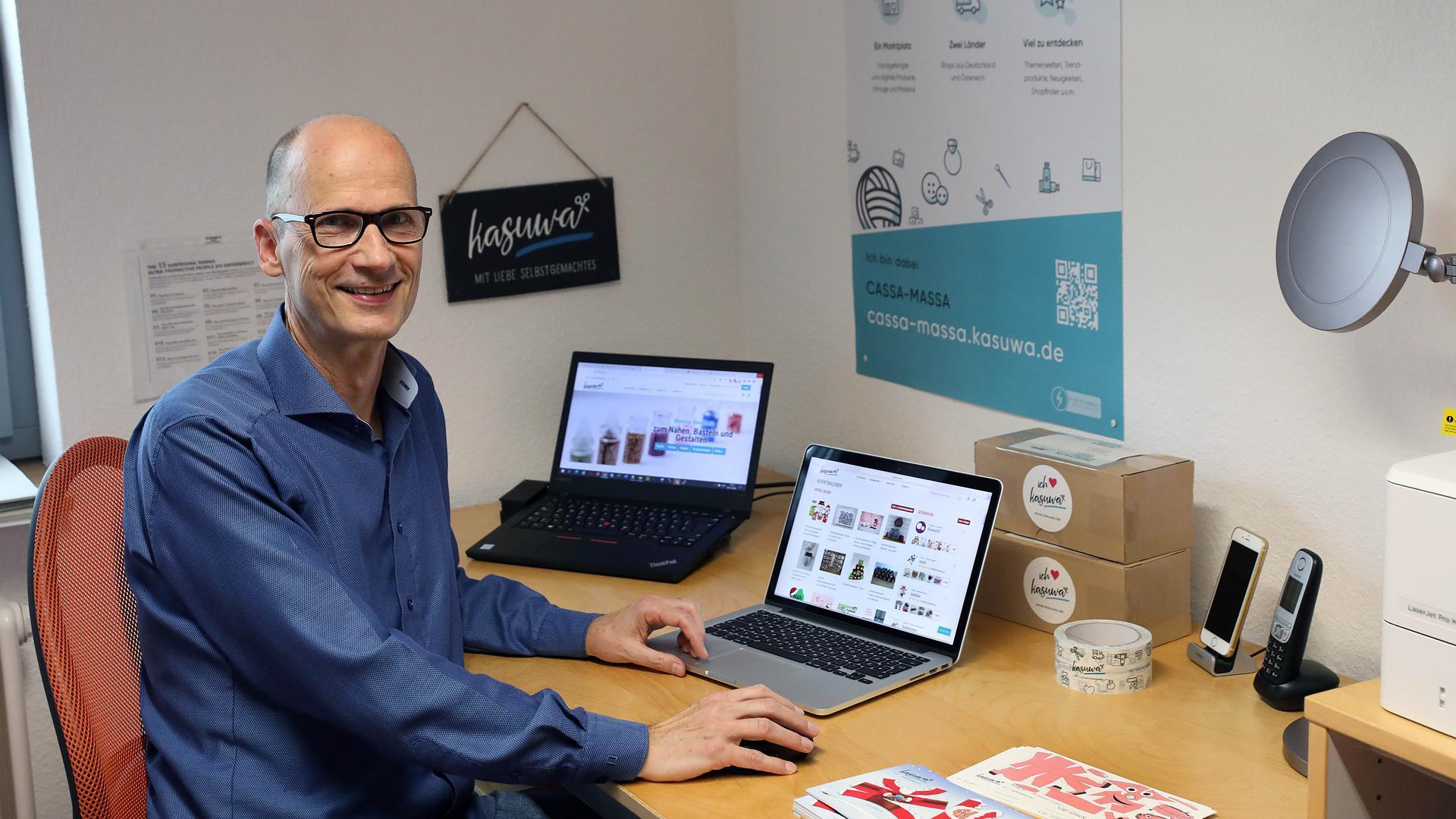 Uwe Günzel sitzt am Schreibtisch, wo zwei aufgeklappte Laptops die Internetseite der Plattform Kasuwa zeigen.