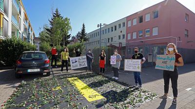 Menschen legen Rosen nieder und halten Plakate in die Höhe