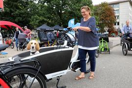 """Hundchen und Frauchen fühlen sich mit dem Lastenrad wohl: Patsy und ihre Besitzerin Heike Mende testen bei der """"Cargobike Roadshow"""" in Karlsruhe verschiedene Modelle."""
