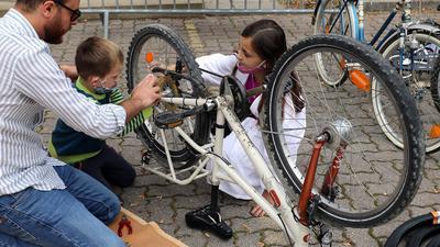 Konzentriert bei der Arbeit: Amour Moayad repariert bei den Lernfreunden ausrangierte Räder. Hier schauen ihm Suela und Syart aus dem Kosovo über die Schultern.