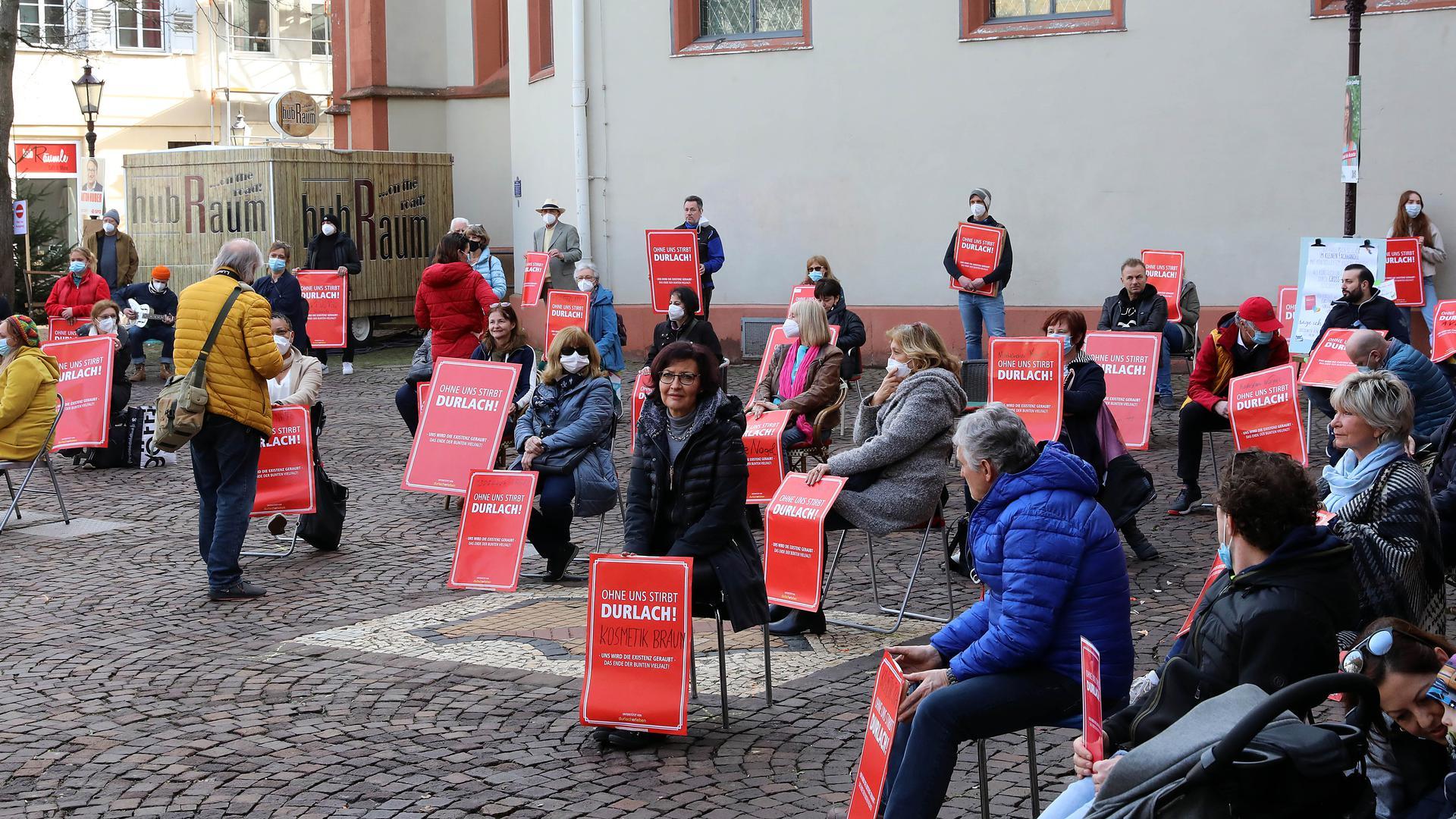 Mahnwache: Geschäftsleute aus der Durlacher Innenstadt weisen vor dem dortigen Rathaus auf ihre teils existenzbedrohende Lage durch den Lockdown hin.