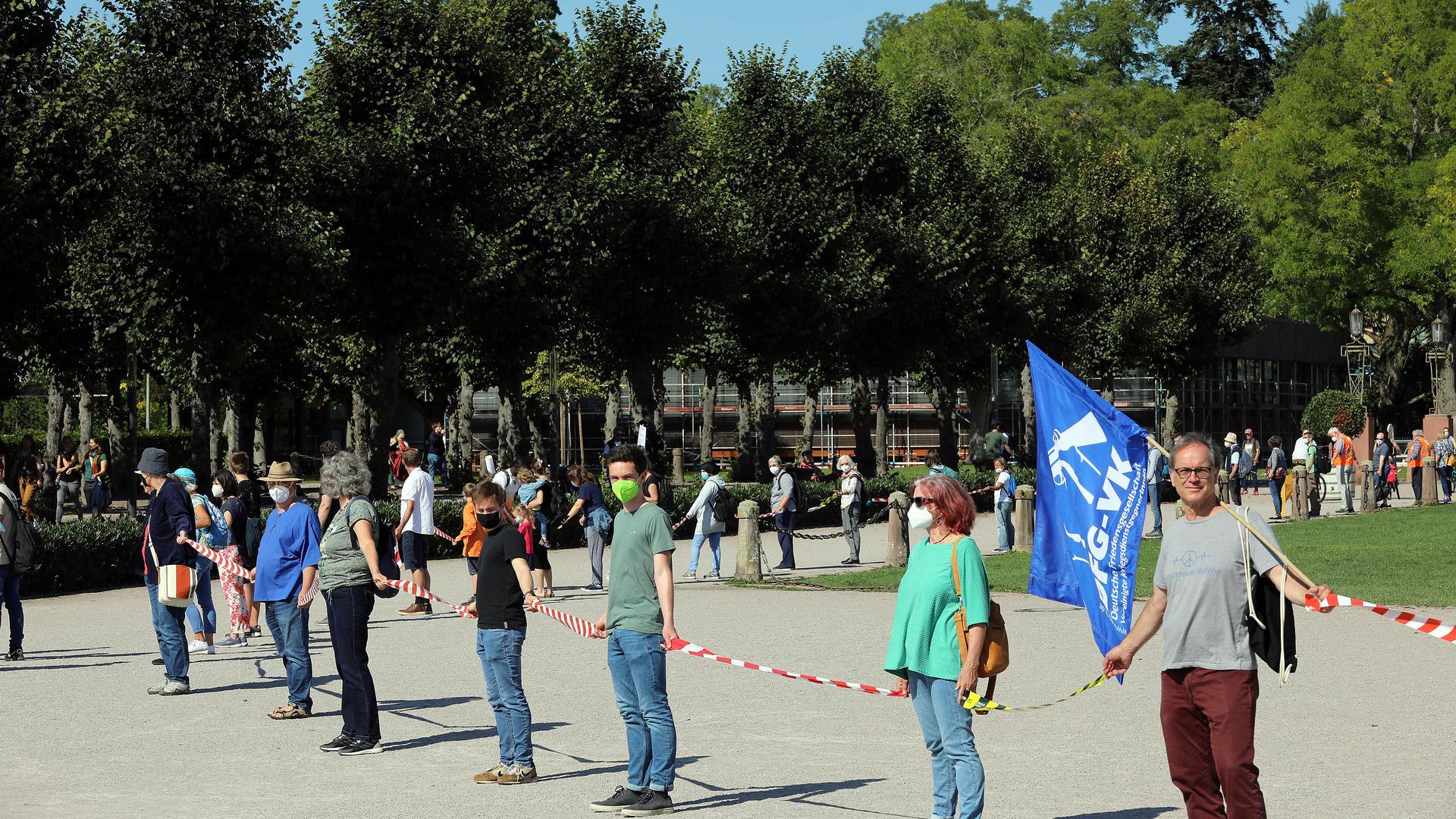 Menschenkette für mehr Menschlichkeit vor dem Schloss Karlsruhe.