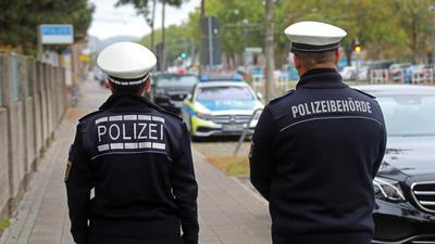 Ein Polizist des Landes und ein Mitarbeiter der städtischen Polizeibehörde laufen nebeneinander auf dem Gehweg.