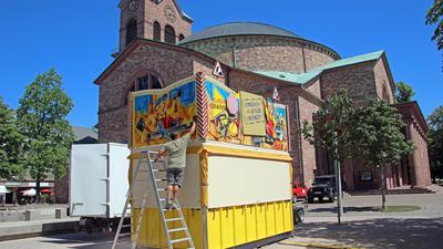 Schausteller Theodor Buntenbroich bereitet auf dem Kirchplatz St. Stephan seine Bude für den Mini-Rummel vor.