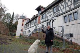 Der Putz bröckelt:  Der historische Frontbau des ältesten Schlossbaus von Karlsruhe steht leer und ist der Witterung ausgesetzt. Jutta Leyendecker, hier mit ihrem Hund Alba, moniert die Zustände.