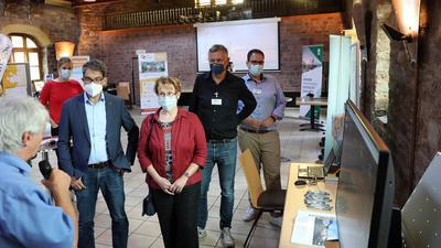 """Schlaue Stromzähler im Fokus: Staatssekretär Andre Baumann und Bürgermeisterin Luczak-Schwarz (Dritter und Vierte von links) informieren sich in der Hoepfner-Burg über das Projekt """"Smart East""""."""